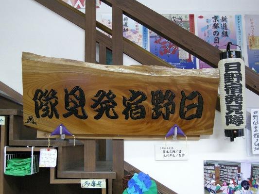 看板の脇に架けられた日野宿発見隊提灯(日野図書館)