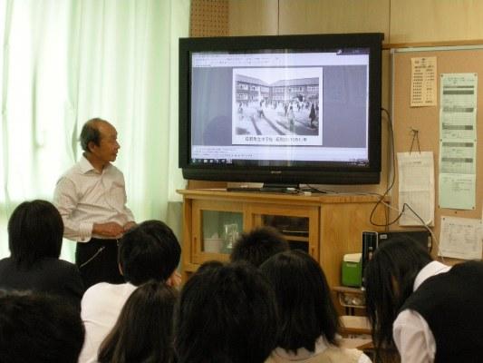 中学校付近の古い写真を見ながら解説する安西さん