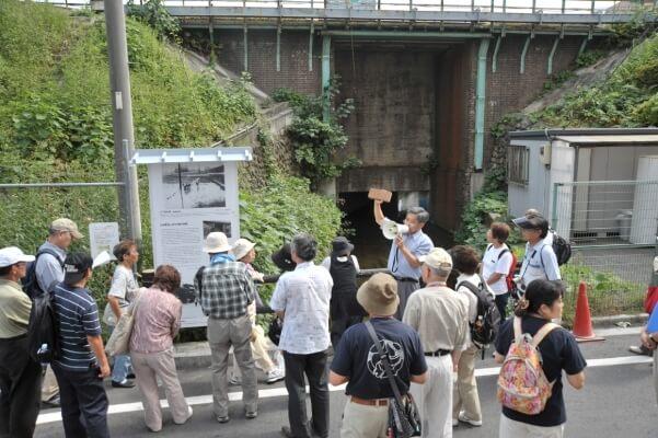 日野駅西側の橋脚前に建てられた谷享司氏製作の看板 日野煉瓦についての解説もつきました 日野煉瓦を持って説明しているのは河野さん