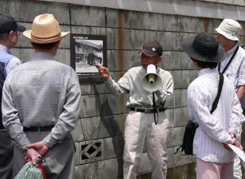 かつて日野町役場があったところにたつ民家の壁に貼られた写真<昭和26(1951)年 松本保氏撮影>を解説する松本保さん(北原在住)。現在の中央公民館入口の道路を 挟んだ西側付近です。