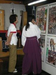 展示された半纏やポスターを見ながら歓談する八坂神社の土淵宮司と志村磨智子さん